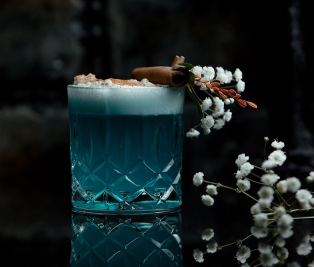 Blue lagoon cocktail glass with white foam and flower decoration