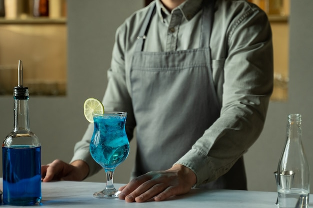 Blue lagoon cocktail is on the bar and a male bartender is standing next to it