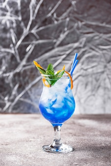 Blue lagoon cocktail  with ice and orange