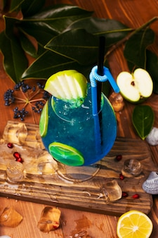 Blue lagoon cocktail with lemon slices in glass on wooden table
