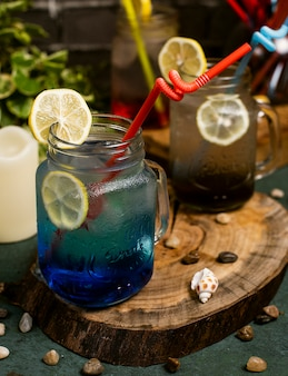 Blue lagoon cocktail with lemon slices inside jar with stick