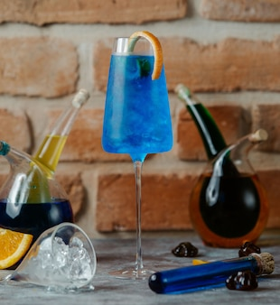 Blue lagoon cocktail with orange stick inside a glass