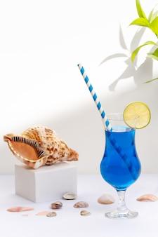 컵 옆에 조개 껍질이 있는 흰색 배경에 블루 라군 음료 컵