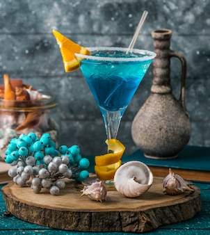 Blue lagoon in martini glass garnished with orange slice