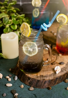 Blue lagoon, red and brown cocktail with lemon slices inside jar with stick