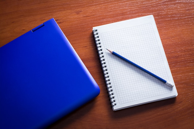 Blue laptop with notebook and pencil on the wooden table
