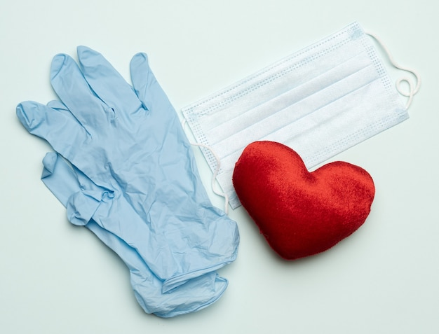 Blue latex gloves and disposable masks on a blue background, hygiene and virus protection accessories for epidemics and pandemics, overhead view