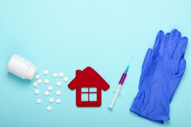 青いラテックス手袋、病院の建物の置物、青い背景の注射器とボトルの丸薬。予防接種。上面図
