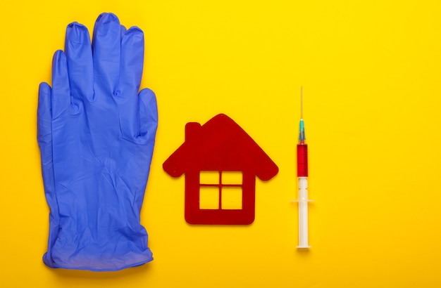 青いラテックス手袋、病院の建物の置物、黄色の背景に注射器。予防接種。上面図