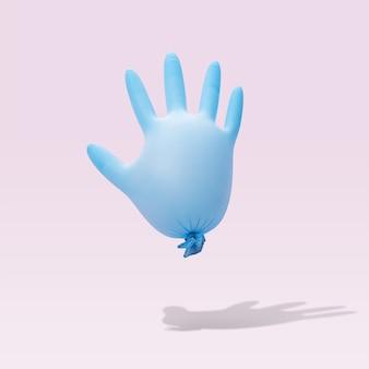 パステルピンクの背景に青いラテックス医療用手袋。