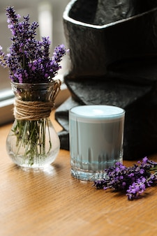 Напиток латте голубой лаванды в стакане на столе с цветами