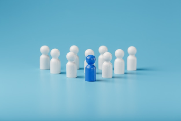 Синий лидер лидер возглавляет группу сотрудников в белом для достижения цели, персонала и набора персонала. концепция лидерства.