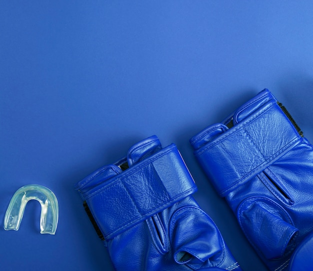 Blue leather boxing gloves and silicone cap for teeth