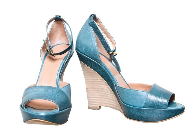 白で隔離される青い革の女性の靴