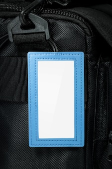Blue leather hanging tag on travel bag background. blank name tag for your design.