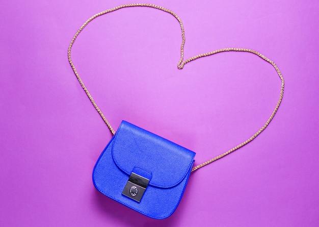 Синяя кожаная мини-сумка с цепочкой в форме сердца на фиолетовом фоне. понятие любви и моды минимализма. вид сверху