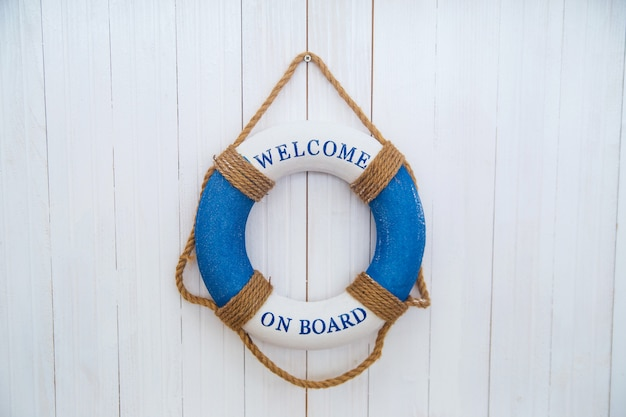 Blue lifebuoy on the white wooden boards with words