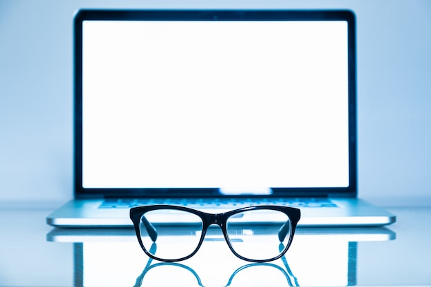 Blue light blockers and laptop in bright background
