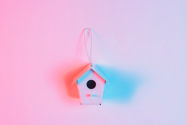 Blue light over the miniature birdhouse with string against pink background