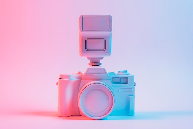 Blue light on vintage painted pink camera against pink backdrop