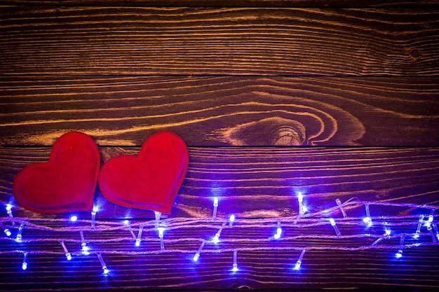 木製の背景に赤いハートと青いライト