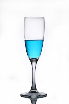 Blue liquid in a champagne glass on a white background.