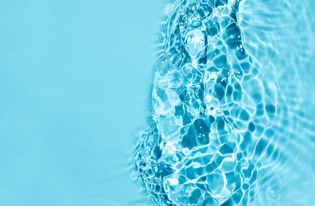Blue liquid colored clear water surface texture with splashes bubbles