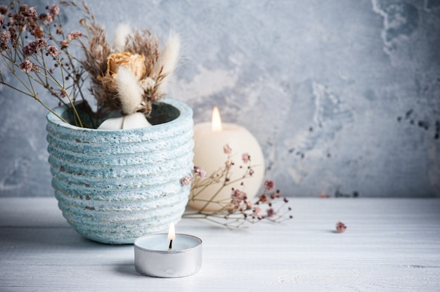 Синяя зажженная свеча и сухие цветы в горшке на белом деревянном столе.