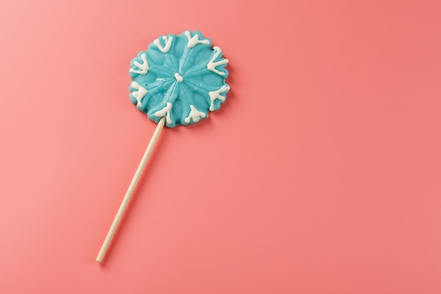 Blue lollipop in the shape of a snowflake on a pink background. sweet sugar lollipop. minimal flat flat composition, free space