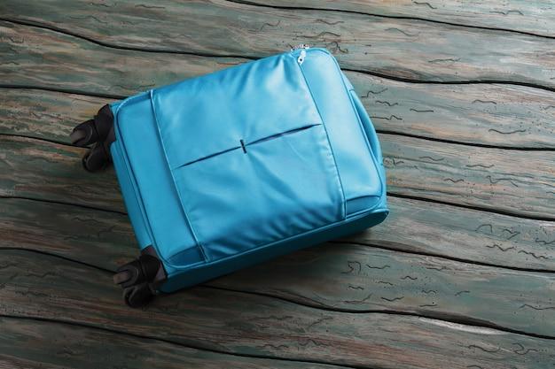 Сумка для багажа синего цвета на колесах. чемодан на зеленом деревянном фоне. пора уходить. не забывайте свой багаж.