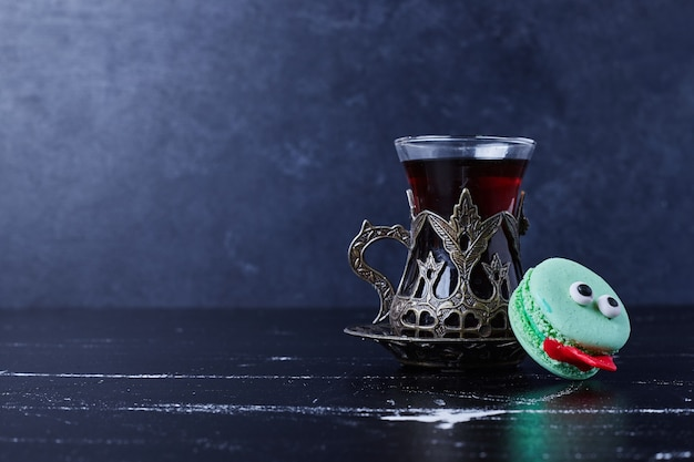 Macaron blu con un bicchiere di tè.