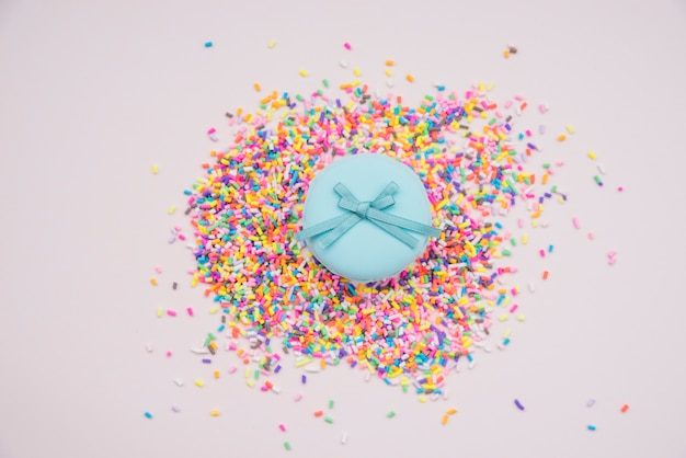 Blue macarons over the colorful sprinkles on colored background
