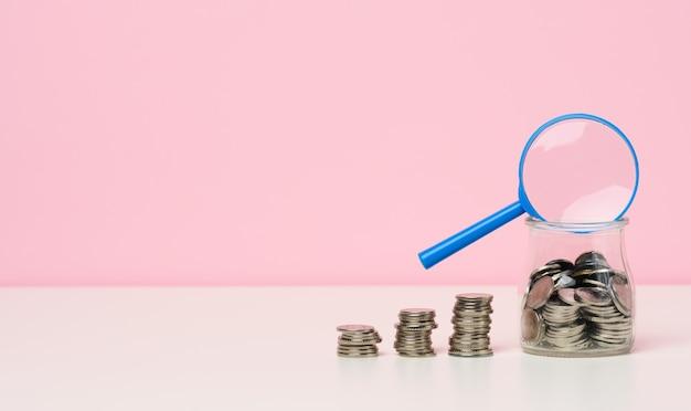 テーブルの上の青い拡大鏡と白いコイン。所得成長の概念、投資の高い割合。新しい収入源、補助金を探す