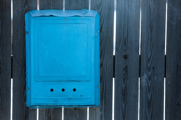 Blue mailbox on a wooden gray fence
