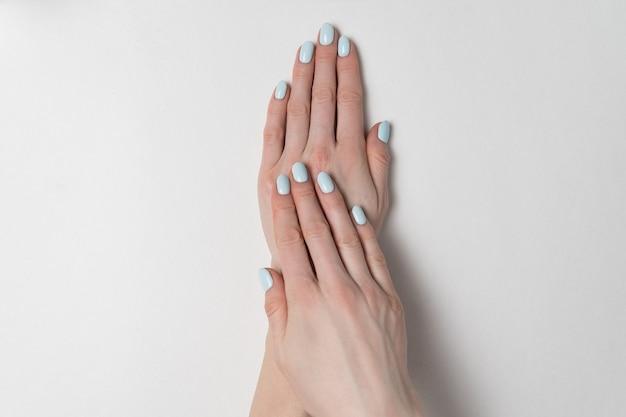 짧은 손톱에 파란색 매니큐어. 흰색 바탕에 손입니다. 가게