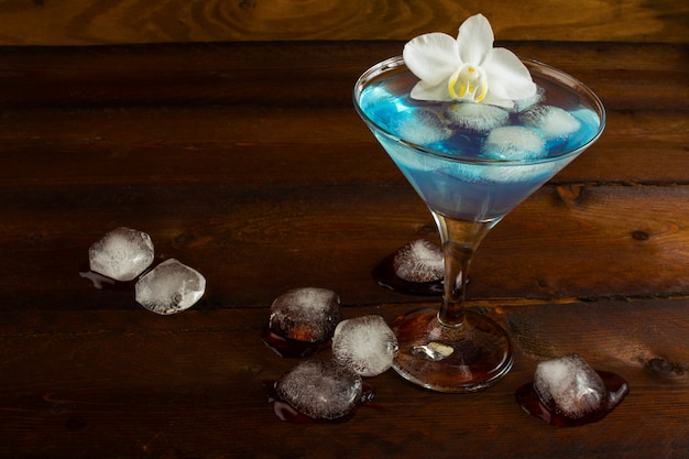 Blue margarita cocktail and white orchid