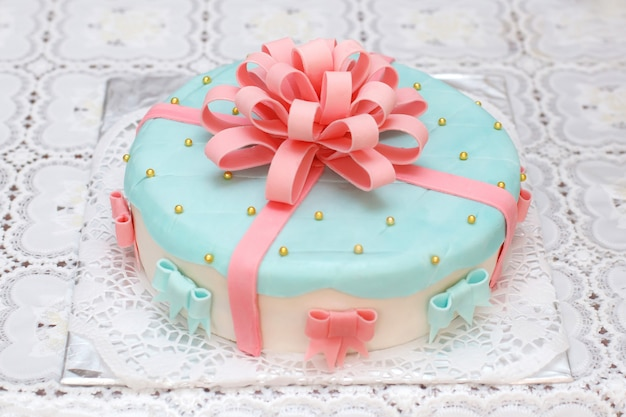Blue mastic cake decorated with pink ribbons, closeup