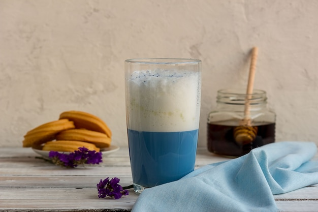 Синий чай матча в стакане латте на столе.