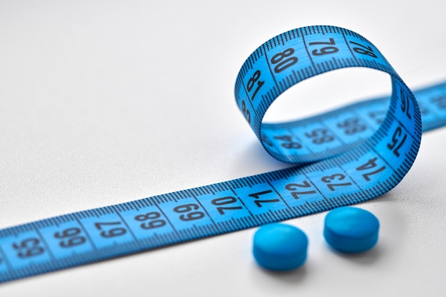 Blue measuring centimeter tape and round diet pills isolated on white background. diet, slimming and weight loss concept.
