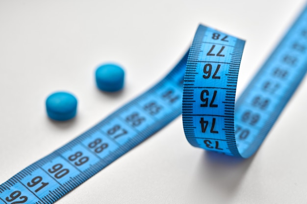 Blue measuring centimeter tape and round diet pills isolated on white background