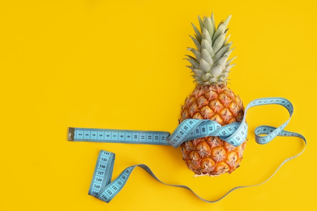 Blue measuring tape around fresh pineapple with copy space as exercise