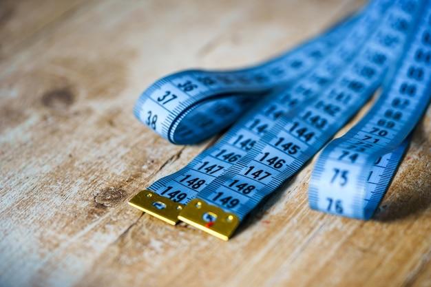 Синяя измерительная лента на деревянном столе. концепция портного. крупный план.