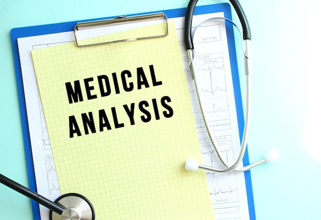 파란색 의료 클립보드에는 medical analysis라는 텍스트가 있는 노란색 종이와 청진기가 밝은 파란색 배경에 있습니다. 의료 개념입니다.