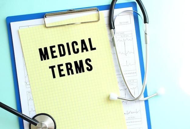 파란색 배경에 의료 용어와 청진기가 있는 노란색 종이가 있는 파란색 의료 클립보드.