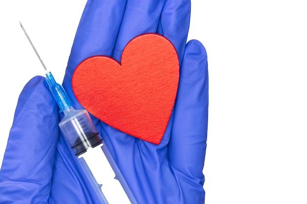 健康とウイルスの概念のための注射器と赤いハートの青い医療用手袋。 covid-19と白い背景の上面図で分離されたコロナウイルスのワクチン接種をクローズアップ