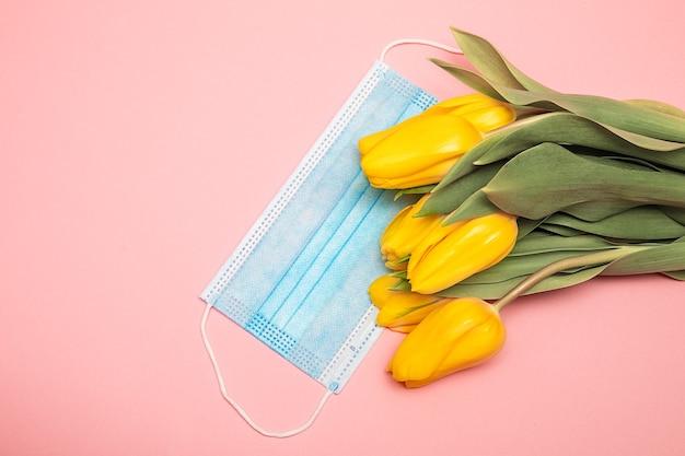 Синяя медицинская маска и желтые тюльпаны на розовом фоне, благодаря концепции врачей. фото cloe-up