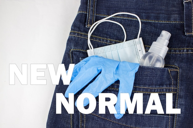 Blue medical mask, gloves and hand sanitizer spray looks out from back jeans pocket with inscription new normal. healthcare concept, covid-19 concept.