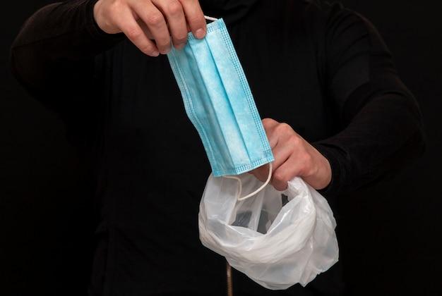 Синяя медицинская маска в руках человека