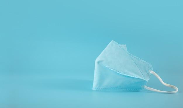 Синяя медицинская маска на столе. коронавирус предотвращение. концепция защиты здравоохранения. остановить эпидемические заболевания. чистый и минималистичный стиль