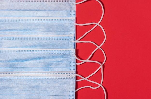 Синие медицинские маски на красном фоне вид сверху профилактика коронавируса